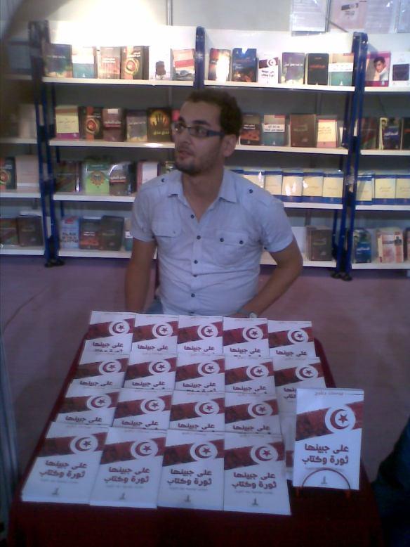 """الكاتب يوسف بعلوج مع مجموعة من نسخ مؤلفه"""" على جبينها ثورة وكتاب"""""""